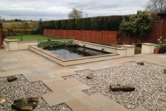 An example of a finished garden landscape redesign including new patio and fencing and a complete refurbishment to an existing pond completed by Perfect Ponds and Landscapes