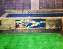 Pond made from railway sleepers with viewing glass built by Perfect Ponds and Landscapes
