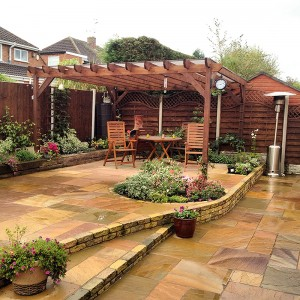 A pergola set in a garden on a patio area