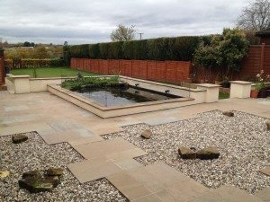 Small pond design with a patio